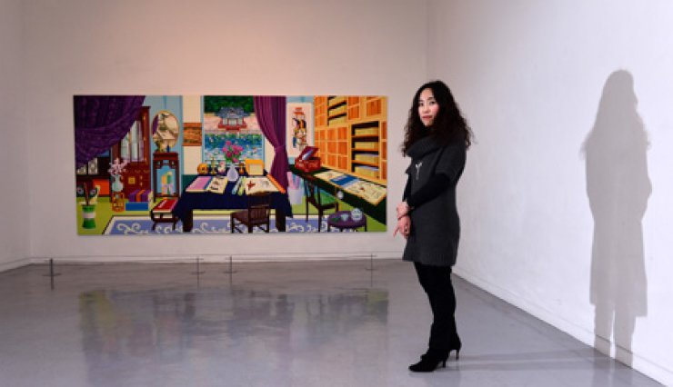 Artist Nam Kyung-min stands next to her painting 'Jeong Sun's Library - Enjoying Seclusion' (2014) during her exhibition at Savina Museum of Contemporary Art in Seoul in December 2014. / Korea Times photo by Shim Hyun-chul