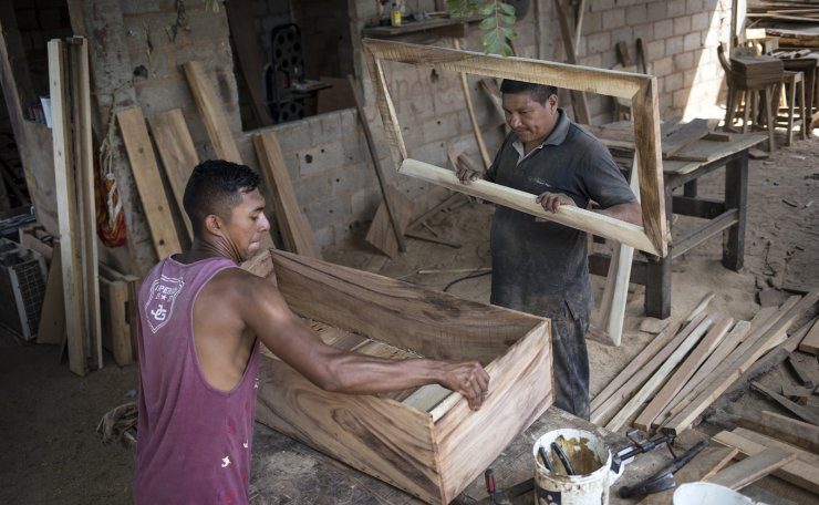 Sergio Morales, right, and Joelvis Cantillo, build a simple coffin at their furniture workshop in Maracaibo, Venezuela, Nov. 20, 2019. Two years ago the carpenters started building coffins for less than $100 instead of furniture due to the high demand for cheaper coffins. AP