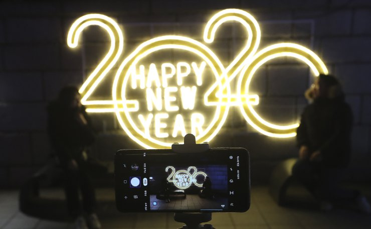 People pose for photos to celebrate upcoming New Year in Seoul, South Korea, Tuesday, Dec. 31, 2019. AP