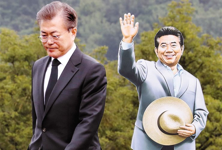 President Moon Jae-in walks off the stage after a speech for former President Roh Moo-hyun, his longtime friend, during Roh's memorial service in Bongha Village, South Gyeongsang Province, May 23. A cardboard figure of Roh stands behind Moon. / Yonhap
