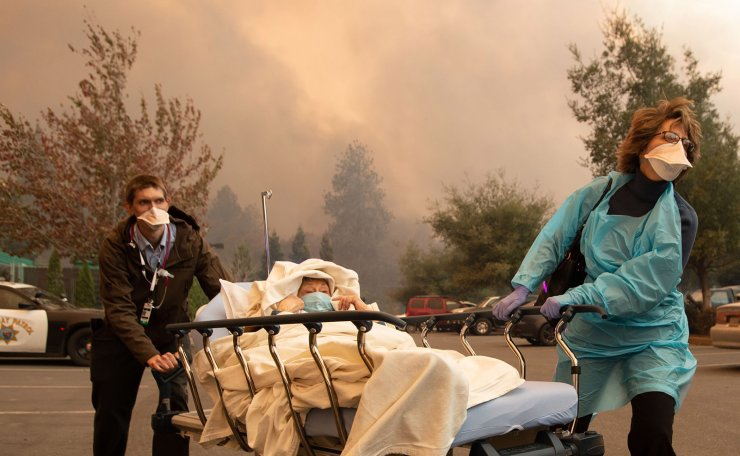 Patients are quickly evacuated from the Feather River Hospital as it burns down during the Camp fire in Paradise, California on November 08, 2018. AFP
