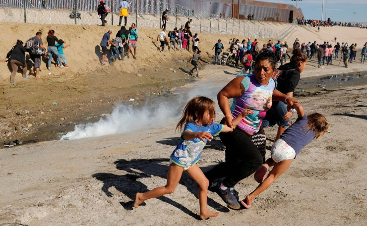 Maria Lila Meza Castro (C), a 39-year-old migrant woman from Honduras, part of a caravan of thousands from Central America trying to reach the United States, runs away from tear gas with her five-year-old twin daughters Saira Nalleli Mejia Meza (L) and Cheili Nalleli Mejia Meza (R) in front of the border wall between the U.S and Mexico, in Tijuana, Mexico November 25, 2018. Picture taken November 25, 2018. Reuters