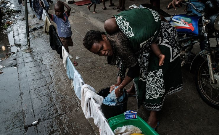 Virgenia Francisco washes cloths with her 6-month-old son on her back, with collected rain water after a strong cyclone hit in Beira, Mozambique, on March 20, 2019. - Five days after tropical cyclone Idai cut a swathe through Mozambique, Zimbabwe and Malawi, the confirmed death toll stood at more than 300 and hundreds of thousands of lives were at risk, officials said. AFP