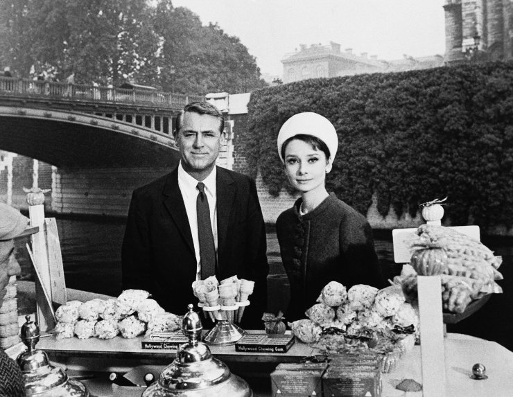 In this October 1963 file photo, actors Cary Grant and Audrey Hepburn are photographed for the film 'Charade,' aboard a boat in the Seine River near the Notre Dame cathedral in Paris.AP