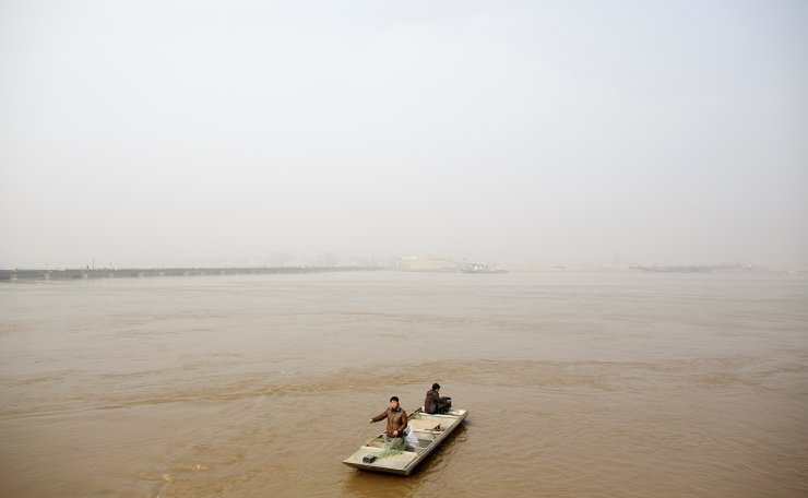 Fishermen Sun Lianxi, 32, and Sun Genxi, 44, travel down the Yellow River to cast their net on the northern outskirts of Zhengzhou, Henan province, China, February 21, 2019. For generations, the Suns plied their fishing boats up and down the Huai and Yellow Rivers, living off their daily catch. Like their grandfather and father before them, brothers Sun Genxi, 44, and Sun Lianxi were born on a fishing boat. China's economic ascent has tantalised the brothers. 'These high-rise buildings have nothing to do with me. They're for others, not me,' Lianxi says.  'We don't have any part in it.'  The Suns were owners of a large houseboat, enough to accommodate their clan of 17 spanning four generations under one weather-beaten roof. But as part of a broad-ranging environmental crackdown, local authorities in 2017 took over the houseboat in the name of minimising water pollution and over-fishing. The Suns now live in tents of tarpaulin and plastic sheets by a floating bridge on the banks of the Yellow River, reduced to fishing from a small dinghy. 'Who knows, my son one day can maybe become something,' Sun Lianxi said. 'But we have to break out of this cycle.' Reuters