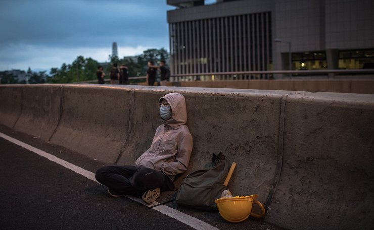 A protester sleeps on a road during a rally demanding a complete withdrawal of an extradition bill, outside the Legislative Council building, in Hong Kong, China, 17 June 2019. EPA