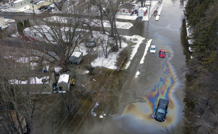 The Sand Creek in Jordan, Minn. has flooded its banks due to a large ice dam and cut off access to the Vally Green Trailer Park, Friday, March 15, 2019. This was the view of Syndicate Street with a few cars and trucks stranded with oil leaking into the water. AP