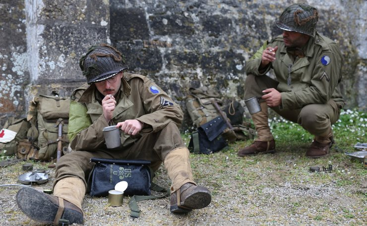 History enthusiasts eat near Sainte Marie Du mont's church, during a re-enactment of D-Day landings to Sainte-Marie-Du-Mont on the Normandy coast, France, 04 June 2019. World leaders are to attend memorial events in Normandy, France on 06 June 2019 to mark the 75th anniversary of the D-Day landings, which marked the beginning of the end of World War II in Europe. EPA