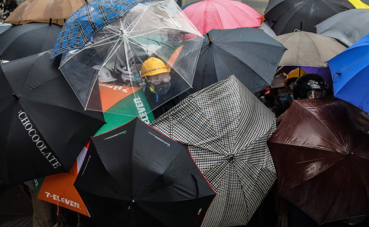 Protesters shield themselves with umbrellas against pepper spray used by the police during a rally against a controversial extradition law proposal outside the government headquarters in Hong Kong on June 12, 2019. AFP