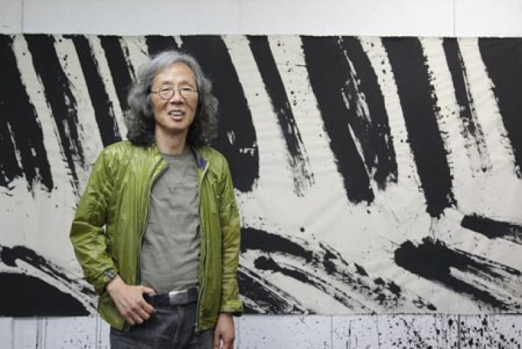 Kim Ho-deuk stands in front of his works at his atelier in Daegu, Monday. Kim has been working with 'meok,' or Korean ink, for over 40 years. / Korea Times photo by Kwon Mee-yoo