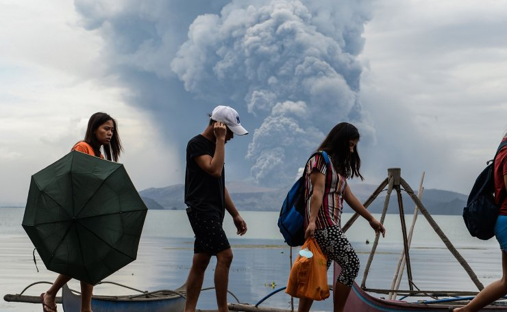 Residents walk past wooden boats as Taal volcano erupts, in Tanauan town, Batangas province south of Manila on January 13, 2020. - Lava and broad columns of ash illuminated by lightning spewed from a volcano south of the Philippine capital on January 13, grounding hundreds of flights as authorities warned of a possible 'explosive eruption'. AFP