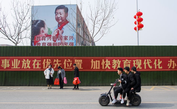 Men ride a scooter past a poster showing Chinese President Xi Jinping on the side of a school building in a newly developed part of Lankao County, Henan province, China February 22, 2019. Reuters