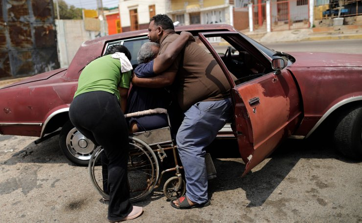 Elimenes Fuenmayor, 65, who has kidney disease, is helped by his sons, as he leaves his house to go to the dialysis centre, during a blackout in Maracaibo, Venezuela April 11, 2019. Reuters