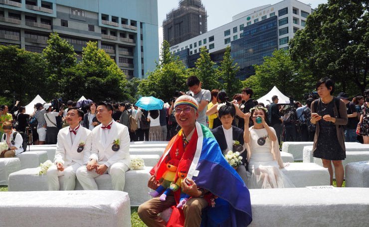 <span>Gay rights activist Chi Chia-wei (C) wears a rainbow flag during a celebration for same sex couples' registering for marraige in Taipei, Taiwan, 24 May 2019. On May 24, many same-sex couples registered for legal union after Taiwan passed a bill to legalize same-sex marriage on 17 May 2019. EPA</span><br /><br />
