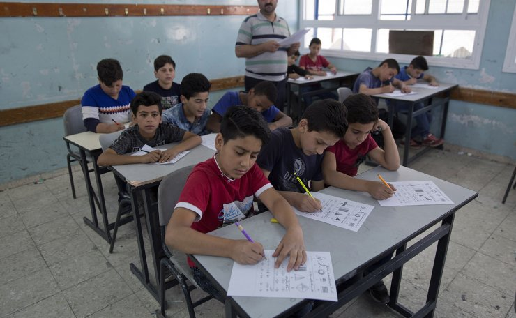 In this Sunday, May 26, 2019 photo, a teacher supervises while Palestinian school children attend a final exam during the last day of the school year, at the United Nations Relief and Works Agency for Palestine Refugees in the Near East, UNRWA, Hebron Boys School, in the West Bank city of Hebron. The effects of U.S. aid cuts have rippled throughout the operations of the U.N. agency for Palestinian refugees, but its sprawling school system, serving 500,000 children across the Middle East, have been hit hardest. Classroom sizes have nearly doubled to 50 students, taxing the patience of children and teachers alike. AP