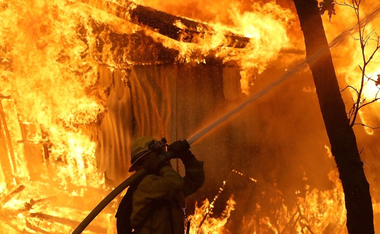 A Cal Fire firefighter monitors a burning home as the Camp Fire moves through the area on November 9, 2018 in Magalia, California. AFP