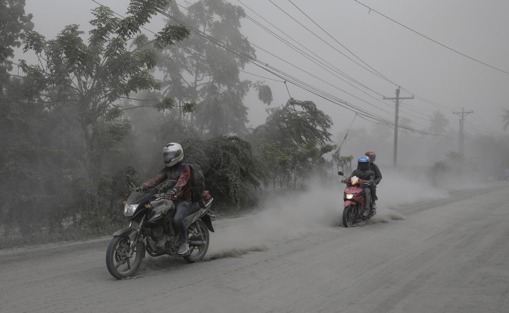 Motorcycles ride along an ash covered road as they evacuate to safer grounds as Taal volcano in Lemery, Batangas, southern Philippines on Monday, Jan. 13, 2020. Red-hot lava gushed out of a volcano near the Philippine capital on Monday, as thousands of people fled the area through heavy ash. Experts warned that the eruption could get worse and plans were being made to evacuate hundreds of thousands. AP