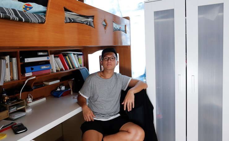 Native Hong Kong resident William Lun, 22, majoring in economy, an aspiring lawyer, who lives with his father and brother, poses for a picture in his 6.5 square meter bedroom of his family's apartment in Hong Kong, China, June 27, 2019. 'I think it's everybody's dream to get a house. It is a Chinese mentality that you have to have a house. It marks a stage in your life when you finally get settled. I want to buy a house in Hong Kong but it's mission impossible,' Lun said. 'Hong Kong should have its own identity along with Chinese identity. Hong Kong is very special; I was born in Hong Kong. I love this place. I cried in the past two weeks many times. Simply seeing what's been happening, my friends getting shot, teargassed,' he added. 'It's sad to see the government being indifferent. They seem to be not listening to the youngsters, they seem to be not caring enough. Two million came out and they are saying, 'Oh, we hear you. But we are still going to press on'.'  Reuters