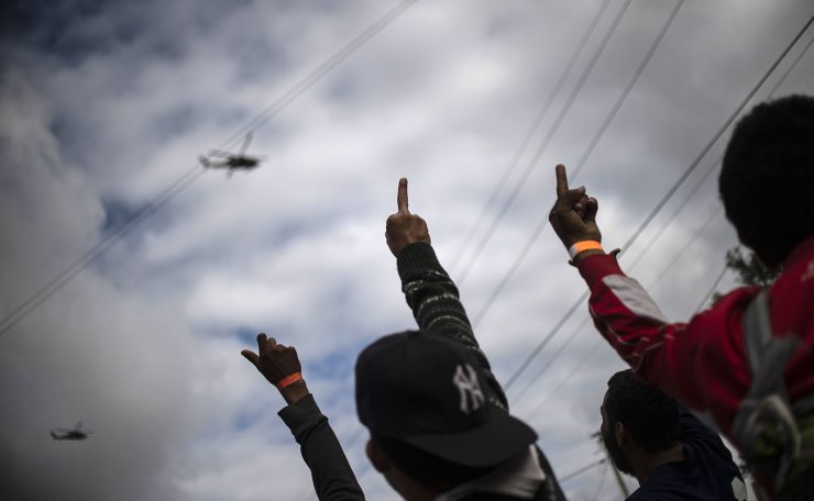 Central American migrants -mostly from Honduras- wanting to reach the United States in hope of a better life, gesture from a shelter in Tijuana, Baja California State, Mexico, as helicopters of the US Customs and Border Protection helicopters overfly the US-Mexico border on November 24, 2018. AFP