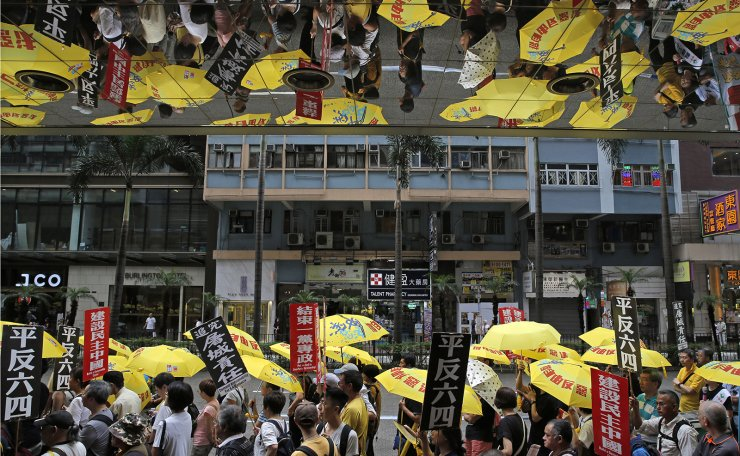 In this Sunday, May 26, 2019, file photo, pro-democracy protesters carry a banner with Chinese reads 'Vindicate June 4th' during a demonstration in Hong Kong. A vigil will be held on June 4 at the Victoria Park to mark the 30th anniversary of the military crackdown on the pro-democracy movement at Beijing's Tiananmen Square on June 4, 1989. AP