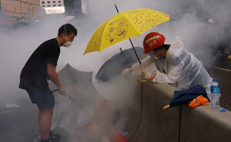 Protesters react to a tear gas during a demonstration against a proposed extradition bill in Hong Kong, China June 12, 2019. Reuters