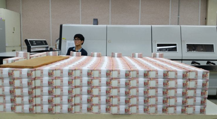 A worker at KOMSCO's Gyeongsan plant last week checks into the printed volumes of the Peruvian currency KOMSCO will deliver by the end of June. / Korea Times photos by Choi Kyong-ae