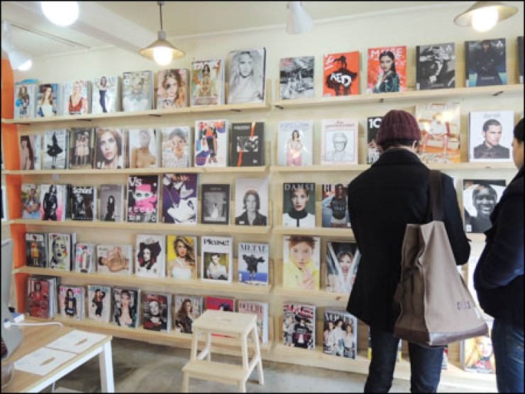 A visitor reads magazines at Paper Muse, the first fashion magazine boutique in Itaewon, Seoul. The shop stocks about 150 kinds of fashion magazines including international editions of Vogue, rare trends, men's fashion and children's magazines.                                       / Korea Times photo by Rachel Lee