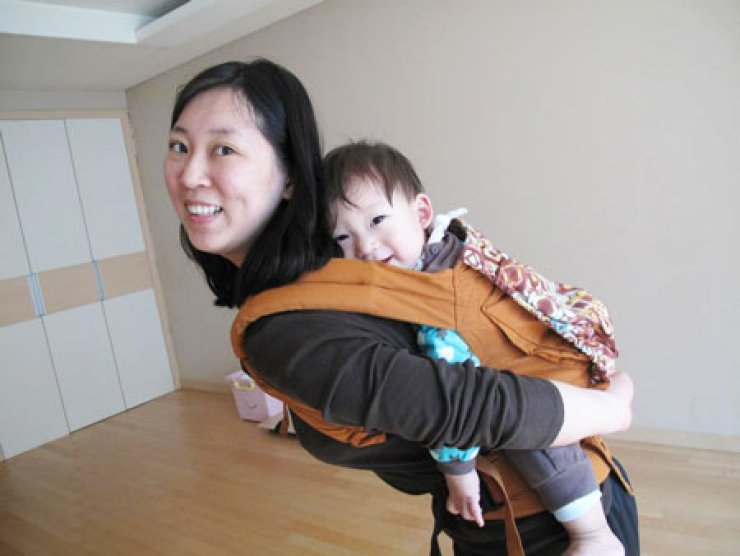 Lee Jung-hee carries her two-year-old son Louis in this recent photograph taken in Ilsan, Gyeonggi Province. Lee and other unwed mothers say they face stigmatization and lack of government support.                                                                                                  / Courtesy of Lee Jung-hee