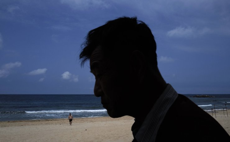 In this Sunday, July 14, 2019, photo, a man stands against while other man walking at Sijung Ho beach in North Korea. The beach is a popular tourist destination for locals and foreigners alike. AP