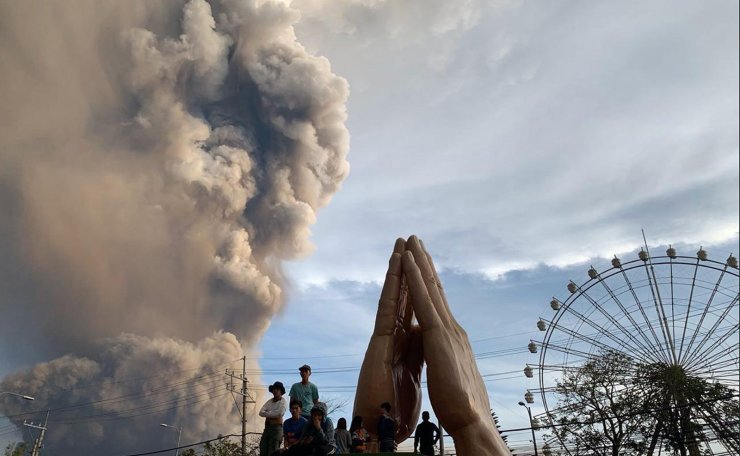 In this Sunday, Jan. 12, 2020, photo, people watch as the Taal volcano spews ash and smoke during an eruption in Tagaytay, Cavite province south of Manila, Philippines. AP
