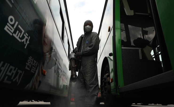 A worker wearing protective gears sprays disinfectant as a precaution against the coronavirus at a bus terminal in Seoul, South Korea, Wednesday, Feb. 26, 2020. Korea Times photo by Choi Won-suk