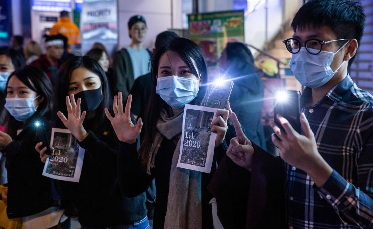 Protesters take part in a human chain rally at the Tsim Sha Tsui district of Hong Kong on December 31, 2019. - Pro-democracy protesters in Hong Kong held hands and formed human chains across the city on Tuesday, as they carried their months-long movement and its demands into 2020 with midnight countdown rallies and a massive march planned for New Year's Day. AFP
