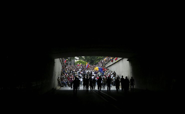 Demonstrators wait for the arrival of Venezuela's National Assembly leader Juan Guaido who has declared himself the country's interim president, at a rally against the government of President Nicolas Maduro in Caracas, Venezuela, Saturday, March 9, 2019. AP