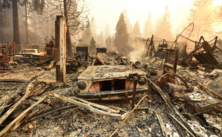 The burned remains of a vehicle and home are seen during the Camp fire in Paradise, California on November 8, 2018. AFP