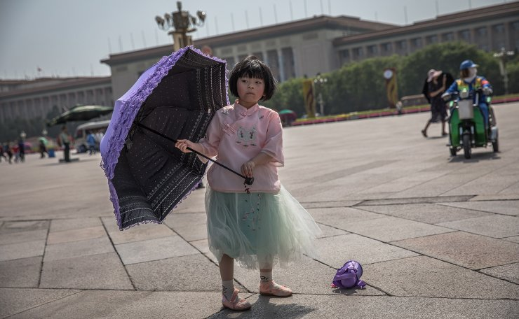 A young Chinese girl stands with an umbrella on the Tiananmen Square in Beijing, China, 16 May 2019. EPA