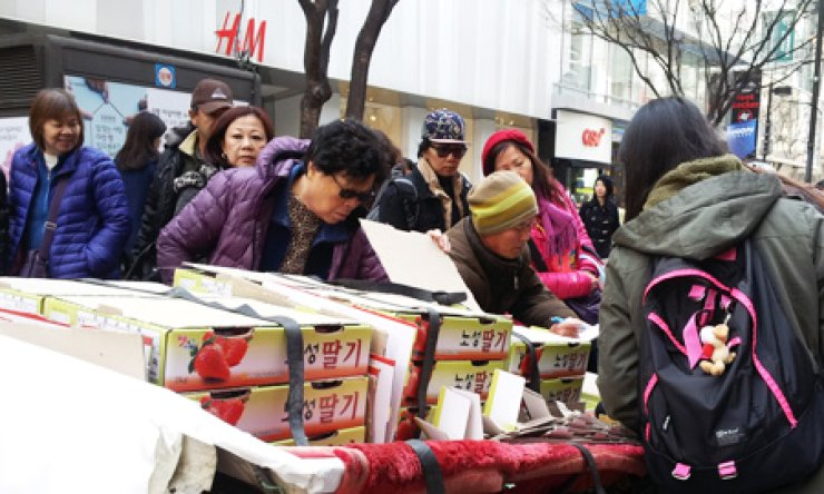 People take a look at strawberries sold by a vendor on the main street in Myeong-dong, central Seoul, Tuesday. Jung-gu Office will phase out all street vendors to make the commercial district more comfortable for tourists to walk around. / Korea Times