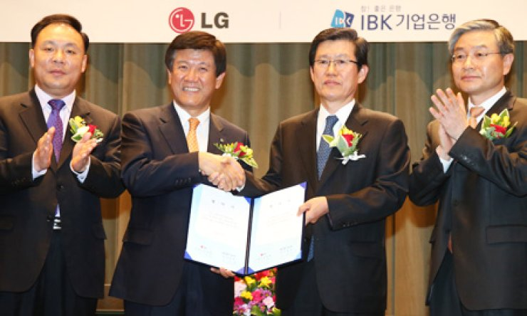 Cho Suk-jae, third from left, LG Chem president, shakes hands with the Industrial Bank of Korea CEO Cho Joon-hee after they agreed to launch a 200 billion-won fund to help its subcontractors at LG's headquarters in Yeouido, Tuesday. / Courtesy of LG Group