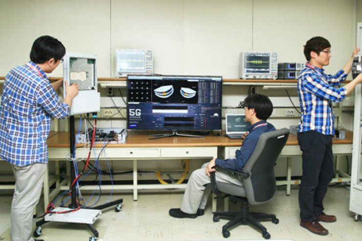 Samsung Electronics employees try out its new data transmission echnology in a 5G network environment at a lab in Suwon, Gyeonggi Province, Sunday. Courtesy of Samsung Electronics