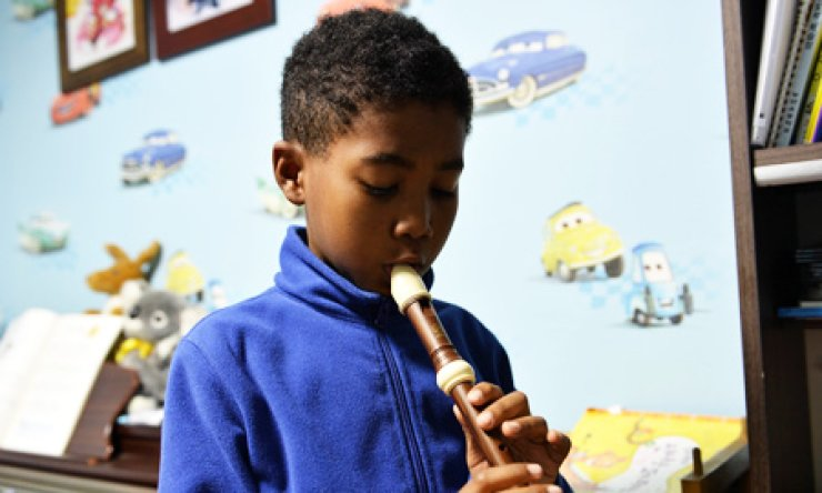Kim Ye-ryu, a nine-year-old Kumchon Elementary School student who was born to a Zambian mother and a Korean father, plays a recorder at his house in Paju, Gyeonggi Province, on Monday. Discrimination issues against multiethnic children have come to the fore as the number of such children has reached nearly 170,000. / Korea Times photo by Shim Hyun-chul