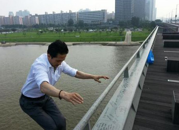Sung Jae-gi, head of Man of Korea, jumps off from a bridge over the Han River in this photo posted on his Twitter account, Friday, a day after he warned of his suicide. Police searched for his body for hours to no avail as of Friday night. / Captured from Twitter
