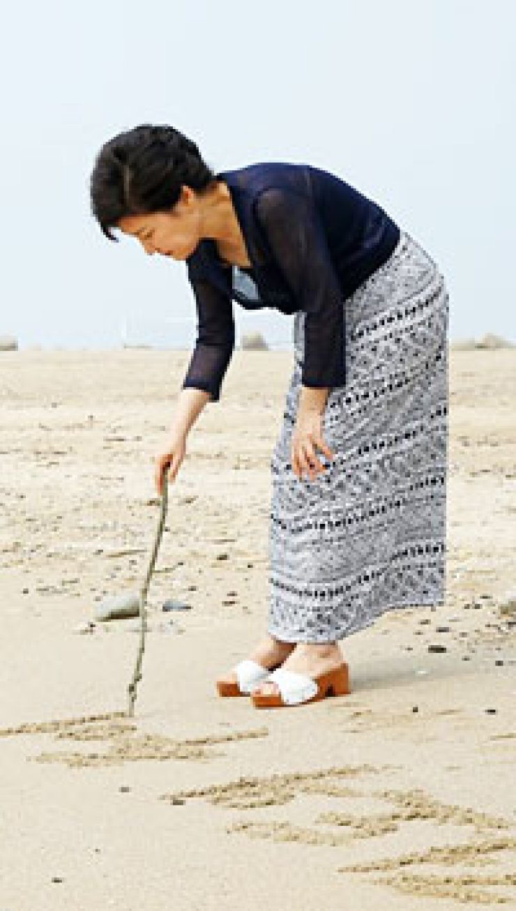 President Park Geun-hye writes words on a beach at Jeodo, an island in South Gyeongsang Province. They read 'Memory of Jeodo.' She uploaded the picture on her Facebook page, Tuesday./ Courtesy of Cheong Wa Dae