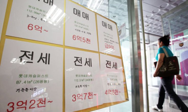 A woman walks past notice boards for home sales and rent posted by a realtor in Seoul, Wednesday. The government unveiled a package of measures to revitalize home trades and stabilize the real estate market on the same day./ Yonhap