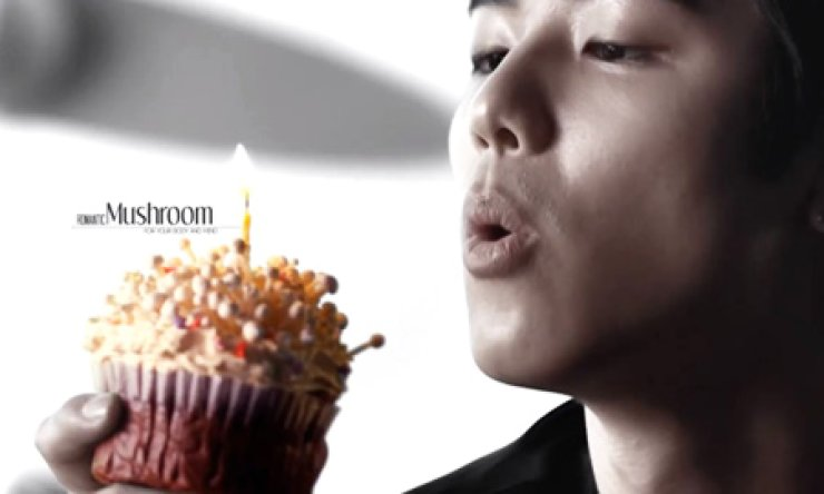 Minhyuk, a member of K-pop group CNBLUE, blows out a candle on a cupcake of Enoki mushrooms in an advertisement for the Korea Agro-Fisheries and Food Trade promoting 'romantic mushrooms.' / Korea Times