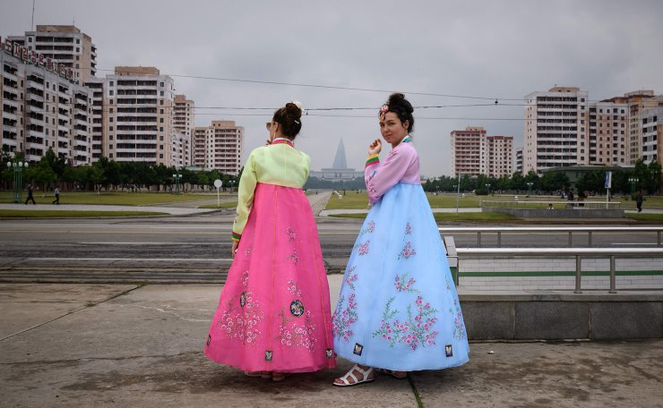 <span>Tourists from Russia wearing traditional Korean dress smoke cigarettes as they stand beside a road in Pyongyang on June 19, 2019. AFP</span><br /><br />