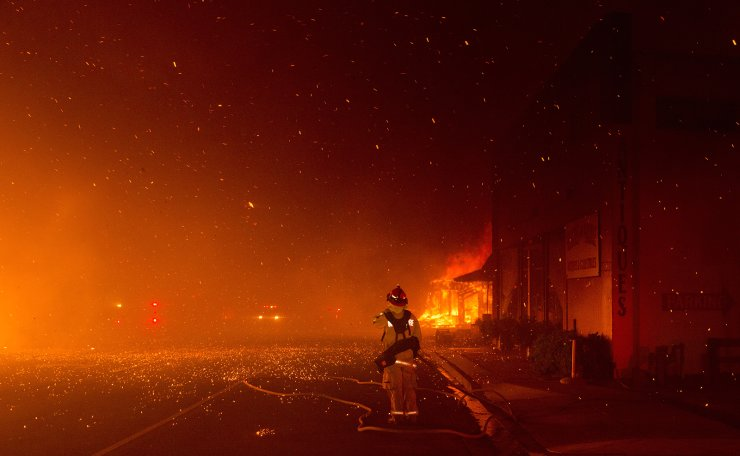 A fire fighter stands at the ready to protect a building across the street, as the Camp Fire burned out of control through Paradise, fueled by high winds in Butte County, California, USA, 08 November 2018. EPA
