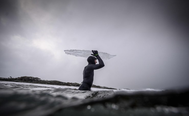 Swedish surfer Pontus Hallin walks into the water with his ice surfboard partly melted at the Delp surfing spot, near Straumnes, in the Lofoten Islands, over the Arctic Circle on February 18, 2019. AFP
