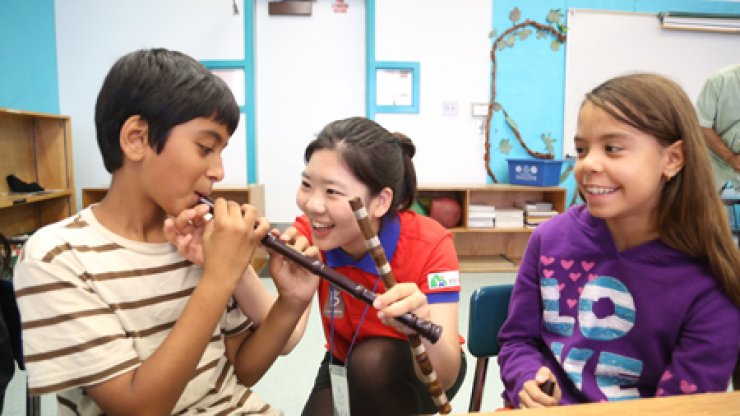 Lim Jung-min, center, a member of Korea Arirang Yurangdan (KAYU) teaches how to play danso, the nation's traditional vertical bamboo flute, to students at Cahuenga Elementary School in Los Angeles, Calif., June 19 last year. The event was part of KAYU's 117-day trip around the world to promote Korean culture and history using Korea's famous traditional folksong, Arirang.                                    / Courtesy of Korea Arirang Yurangdan