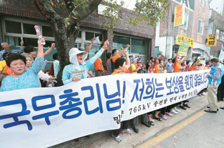 Residents of Miryang, who are opposed to transmission towers to be built across their villages, protest in front of a district office on Sept. 11, the day Prime Minister Chung Hong-won visited the area in South Gyeongsang Province. The protesters' placard reads, 'Prime Minister! We do not want compensation.' / Yonhap