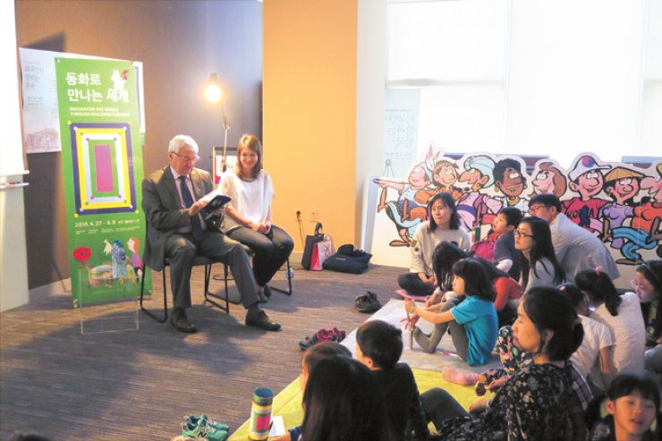 Polish Ambassador to Korea Krzysztof Majaka, left, reads out a Polish version of 'The Little Prince' to parents and their chilren during a program 'Book Reading for Children by Ambassadors in Korea,' a part of the Korea Foundation' exhibition 'Encounter the Worldthrough Children's Books' at the KF Gallery in Seoul on May 5. / Courtesy of the Korea Foundation