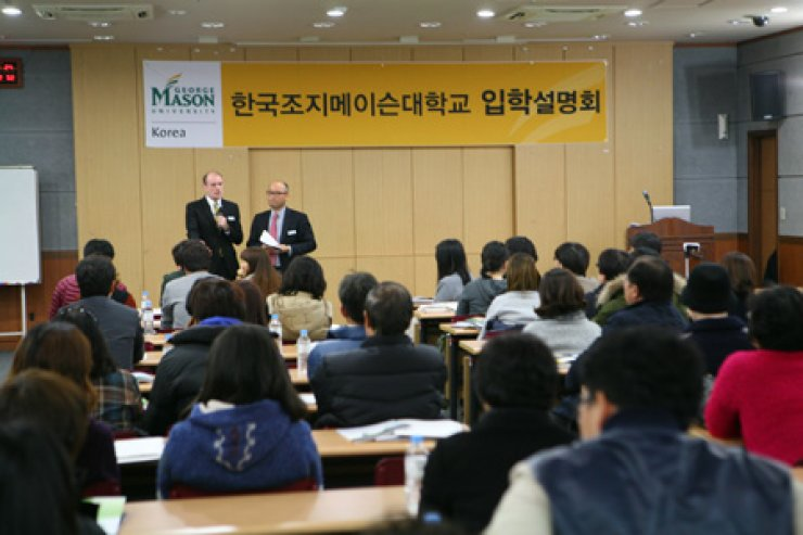James Burke, standing left, director of events and outreach at George Mason University explains to students and parents about the admissions policy of the school's Songdo campus located in Incheon, during a briefing session at the Seoul Trade Exhibition and Convention building, Dec. 15./ Courtesy of George Mason Korea